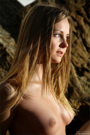 Красивая девка загорает на скалах