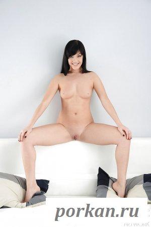 Красивая девушка с чёрными волосами на кровати