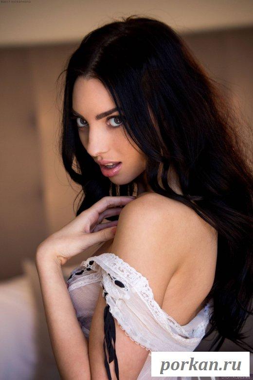 Красивая девушка раздевается в спальне