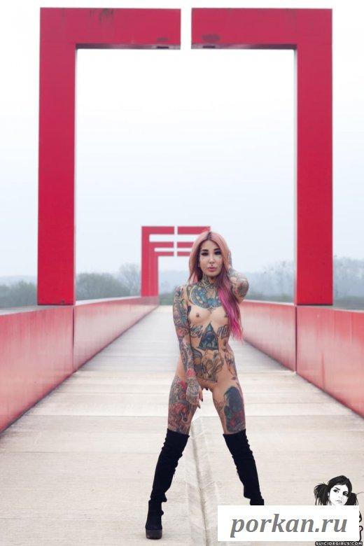 Обнаженная азиатка с татуированным телом позирует на мосту